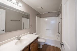 white bathroom with toilet, sink, and tub/shower